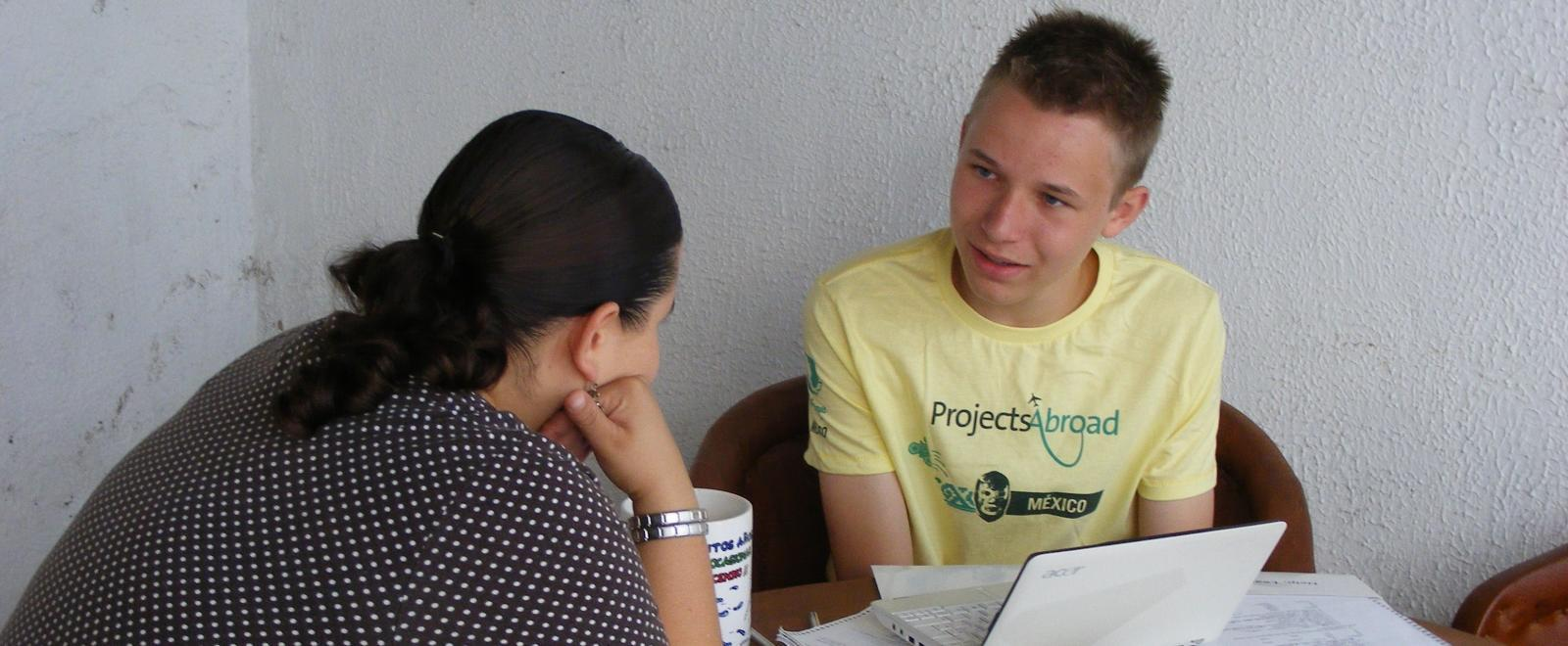 A young volunteer receives a Spanish language lesson as part of his induction at the Projects Abroad office.